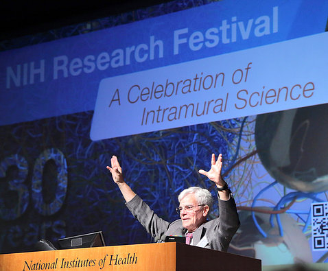 Dr. Gottesman holds hands up high at the podium, in front of slide that reads NIH Research Festival A Celebration of Science