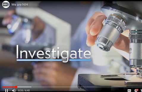 "A screenshot from the NIH welcome video shows the word ""investigate"" next to a hand hovering over a microscope."
