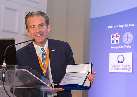 Dr. Constantine Stratakis holds award at ceremony in Athens.