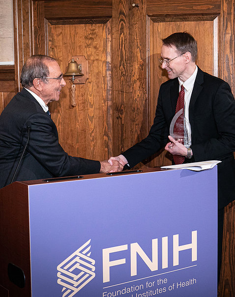 Gallin shakes hands with awardee Kochenderfer at podium draped with purple FNIH banner.