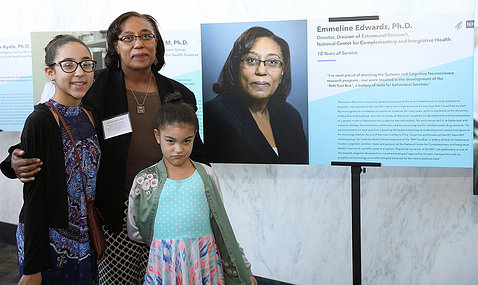 Dr. Emmeline Edwards of NCCIH and her granddaughters next to poster with her photo