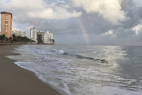 A rainbow shines through the clouds over a beach