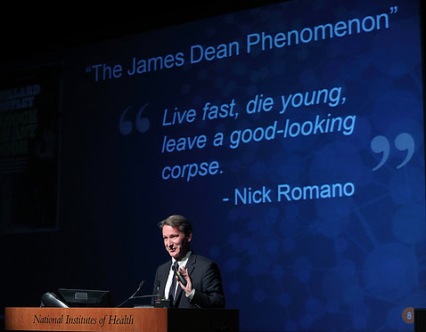 Dr. Sharpless in front of slide with the quote Live fast, die young, leave a good-looking corpse.