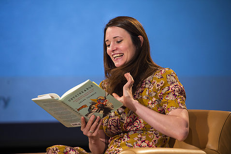 Thomson seated on stage reading from her book