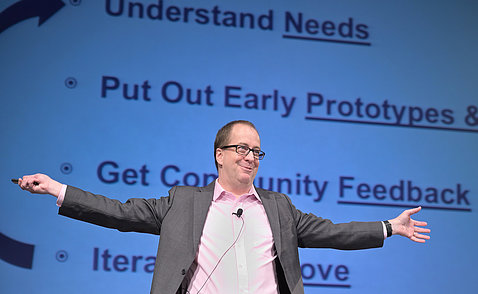Eric Dishman smiles with outstretched arms as he explains the All of Us innovation process.
