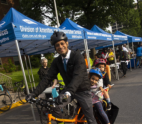 A smiling Dr. Chittiboina on his electric cargo bike with his two young kids in tow