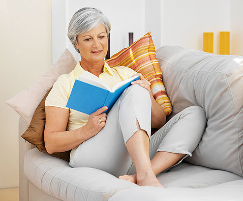 Woman with gray hair reads on sofa