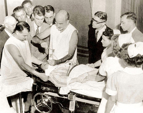 Black & white image of Freeman, not in surgical scrubs or mask, performing lobotomy surrounded by onlookers.