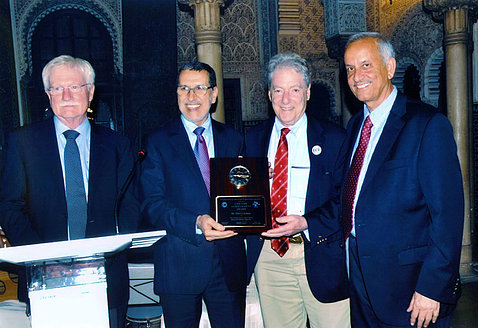 A smiling Dr. Gardner holds award, poses with NIAAA's Dr. Koob, the prime minister of Morocco and Dr. Ali of IDARS.