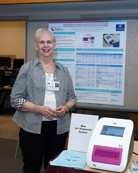 Gaydos stands beside diagnostic instrument, with scientific poster behind her.