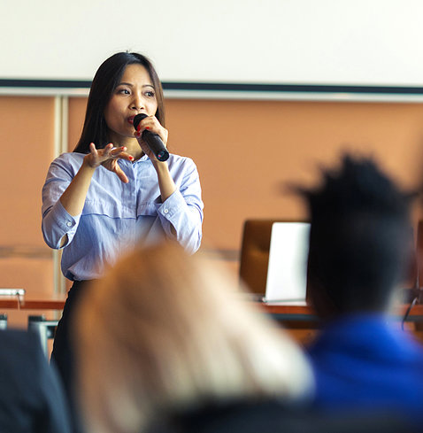 A woman standing speaks to an audience at a business presentation