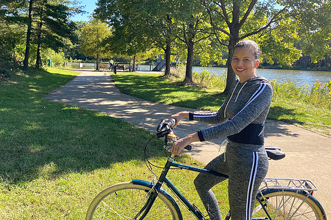 Fitzhugh on her bike with the trail and a lake behind her