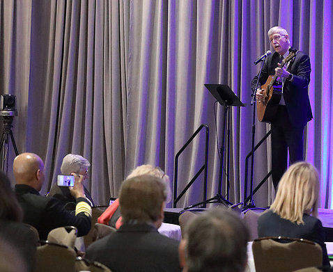 Dr. Collins stands on stage with his guitar singing into the mic to hundreds assembled in the Hyatt ballroom.