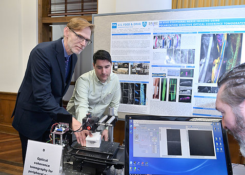 Tromberg and Monroy manipulate an imaging device as Hammer views screen, with scientific poster behind them.