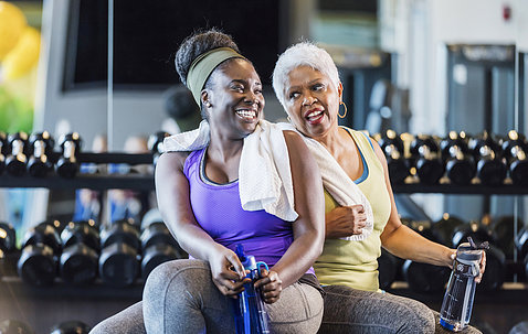 Two women sit smiling with water bottles in front of hand weights at a gym.