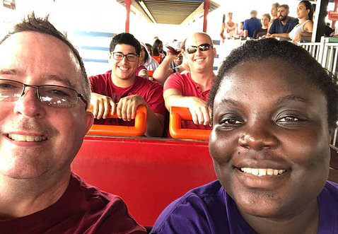 Jason and Chris, each seated next to a young adult they previously fostered, on a roller coaster.