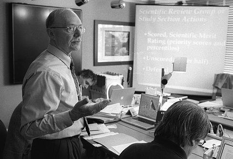 A black & white photo of Dr. Remondini standing near a presentation slide in a conference room