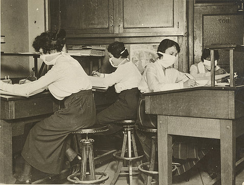 A black & white photo shows four women wearing masks working at their desks.