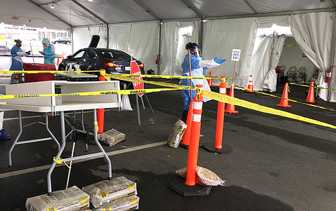 Outside, under a tent, responders in gowns, masks and gloves stand ready to test people for covid at a drive-through testing facility.