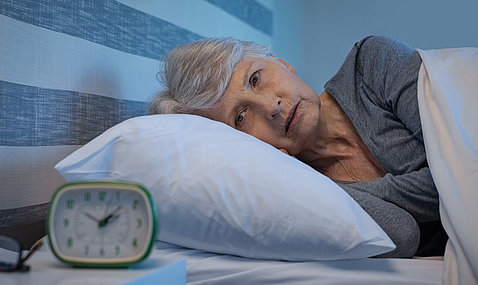 An older woman lies awake in bed next to an alarm clock on her nightstand.