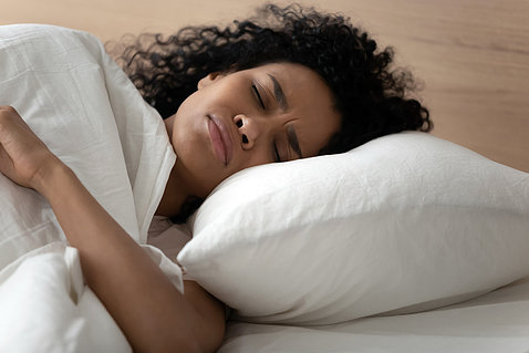 A woman lies on her pillow struggling to sleep.