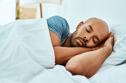 An African American man lays asleep in bed.