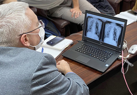 Childs, wearing a mask, looks at x-rays on a laptop.