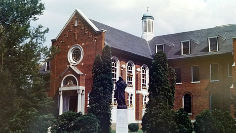 Historic image of the Cloister building with statuette in front