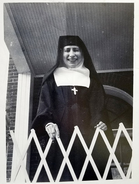 Sister Mary Rita in habit smiles from upper floor room balcony
