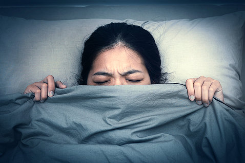 A woman in bed pulls her blanket up past her nose