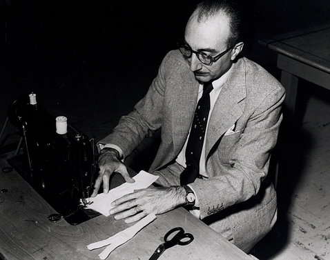 Archival photo shows DeBakey stitching strips of Dacron using a sewing machine, with scissors on table next to him