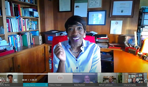 A smiling Harris sits at her desk talking to her videoconference audience