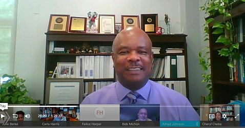 A smiling Dr. Johnson at his desk asks Harris an audience member's question via videocast.