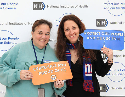 "Two NIH'ers hold signs: ""protect our people and our science"" and ""cyber safe and proud of it."""