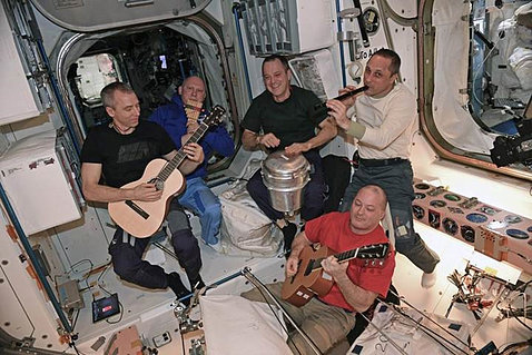 "Astronauts play musical instruments, including a ""drum"" consisting of a repurposed solid waste container."