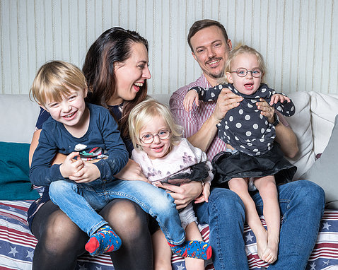 Niclas and Jessica, with their 3 young children, all smiling, sit together on a bed