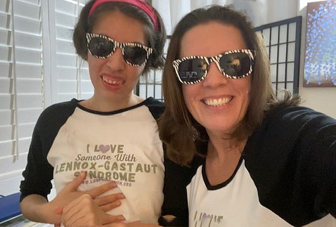 """A smiling young Savannah in an """"I Love Someone with Lennox-Gastaut syndrome"""" shirt, with her smiling mom; both are wearing sunglasses."""