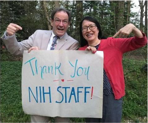"""Holland and Pao, both smiling, hold up a poster board sign that says, """"Thank you NIH staff!"""""""