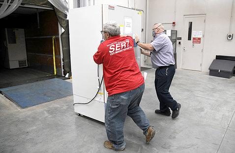 Two men roll large freezer toward truck.