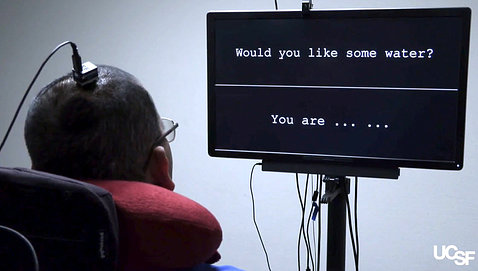 Person with an electrode attached to head faces a computer screen showing a full sentence and words of another sentence.