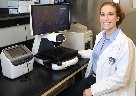 Sadtler sits in lab in front of a computer screen and microscope.