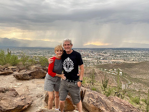 Atop a large rock, Warren and Beiser smile toward camera, with a stormy sky and a cityscape behind them.
