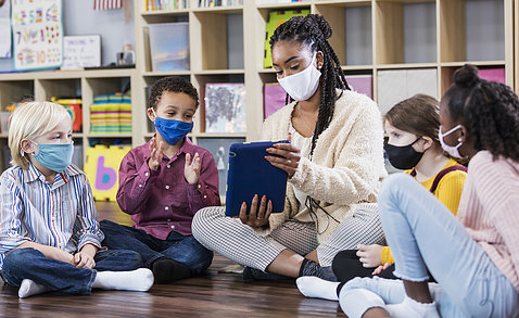 A teacher is seated holding up a tablet for 4 students seated around her, all wearing masks.