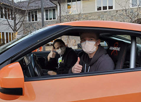 Jen and Luke give thumbs up sitting in Driven to Cure car in front of the Children's Inn.