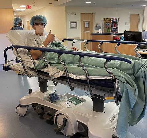 Luke gives thumbs up on hospital bed in hallway of the Clinical Center.