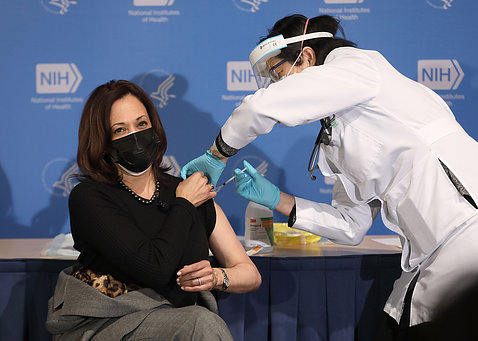 Seated with left arm exposed, Harris receives her shot from Judy Chan.