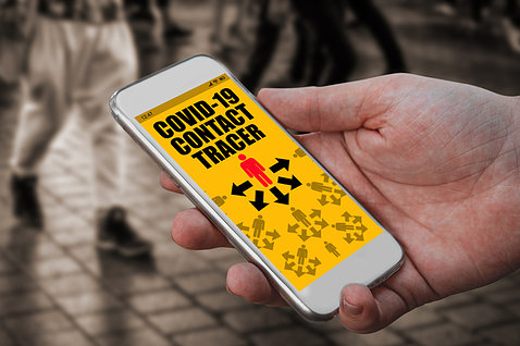 A hand holds a smartphone with bright yellow screen showing covid contact tracing app, in a crowd of people