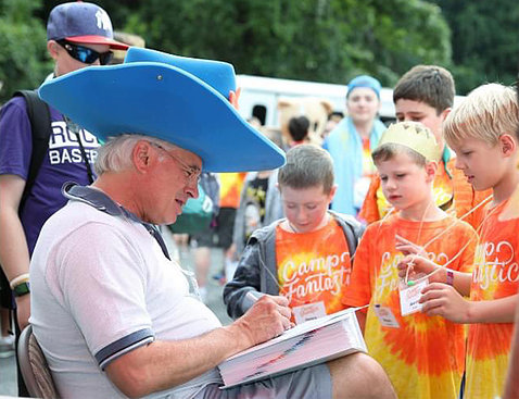 Chanock in a big blue hat sits drawing on a paper as 3 young children in orange Camp Fantastic t-shirts look on.