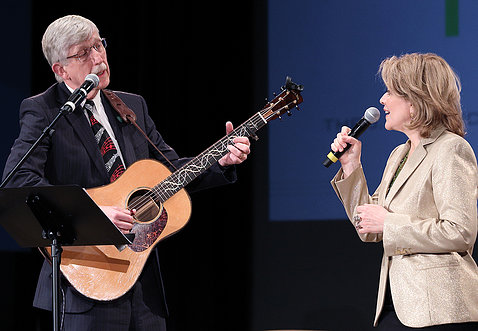 Collins holding guitar and Fleming holding a microphone sing together on stage in Masur Auditorium in 2019.