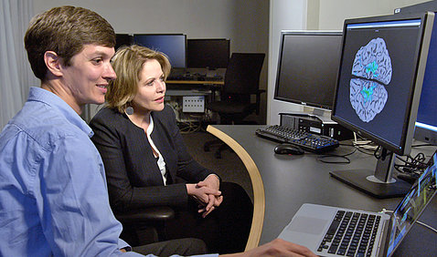 A researcher and Fleming sit in front of a computer screen showing an image of her brain with different colors reflecting when her brain was activated during her MRI.